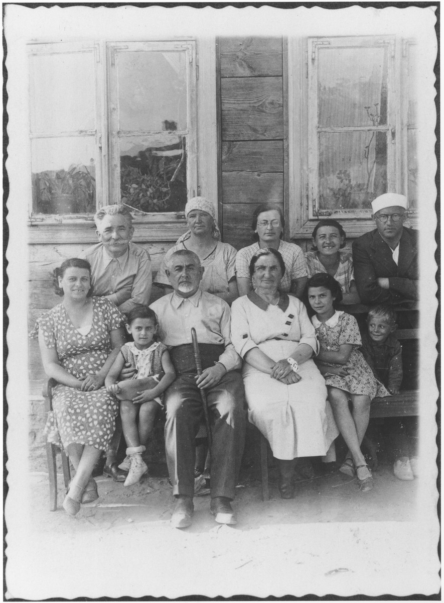 Members of the Taca and Berkowicz families pose outside a farm house where they stayed while on vacation.  Pictured in the front row from left to right are: Bina Berkowicz, Basia Berkowicz, Szmul Taca, Ela Taca, and Basia Chudy.  In the back row are: Natan Taca, farmer's wife, Mania Taca, Fela Taca and Chaim Ber Berkowicz.