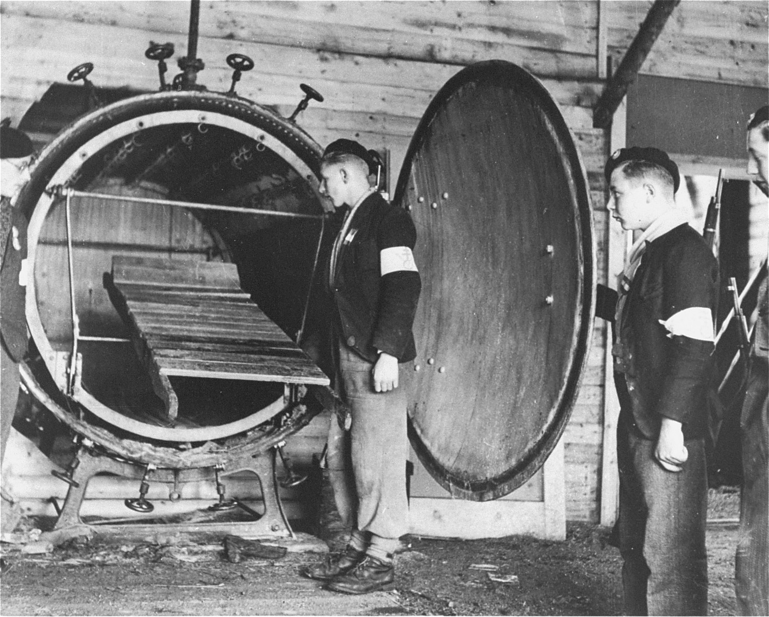 Men with the French forces of the Interior examine a tank containing a wooden stretcher that is believed to be an experimental gas chamber.