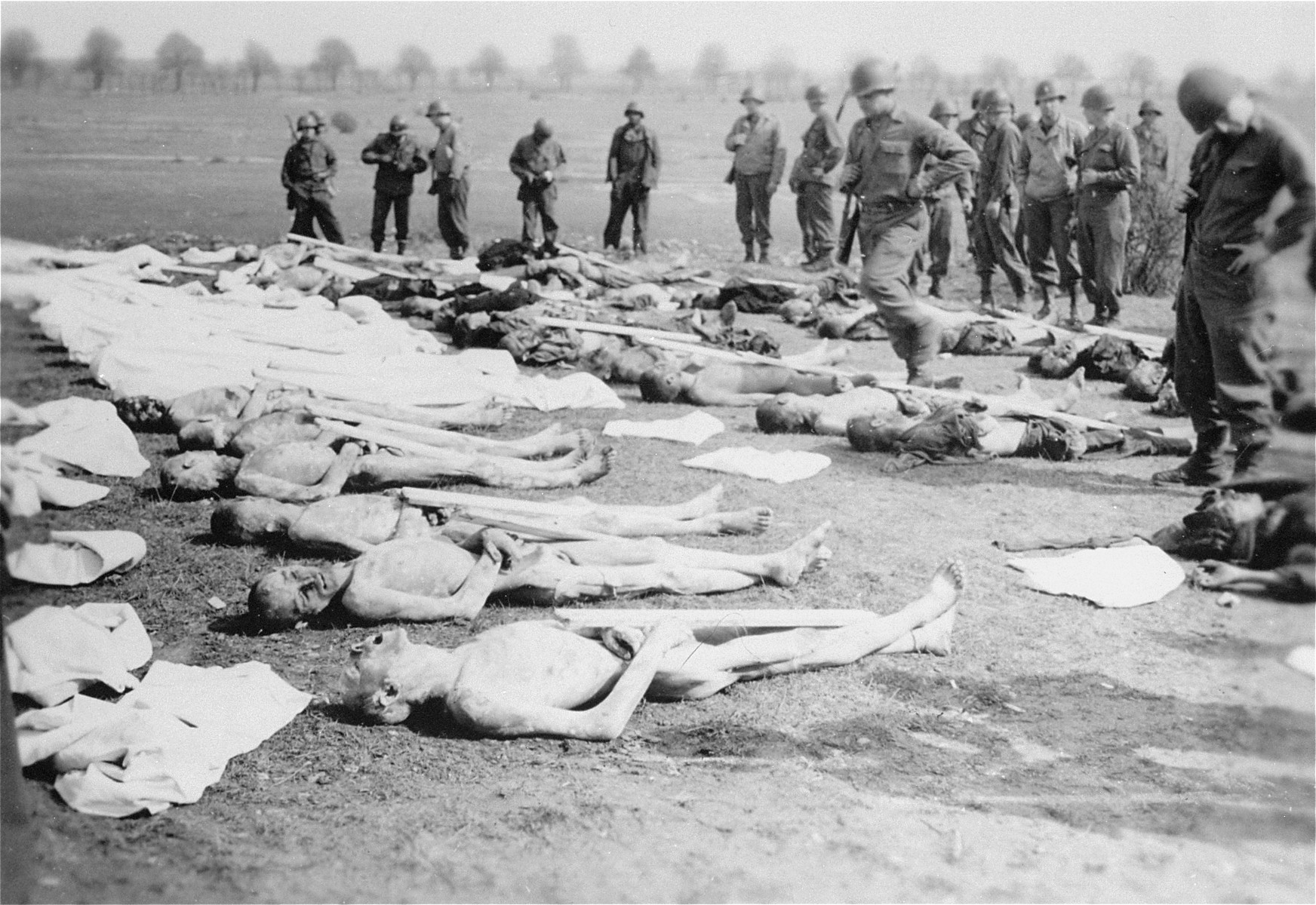 American soldiers stand among corpses laid out for burial by German civilians conscripted to clean up the Ohrdruf concentration camp.  Due to a lack of information about the names of the dead, each body was assigned a number to be placed on the grave marker.