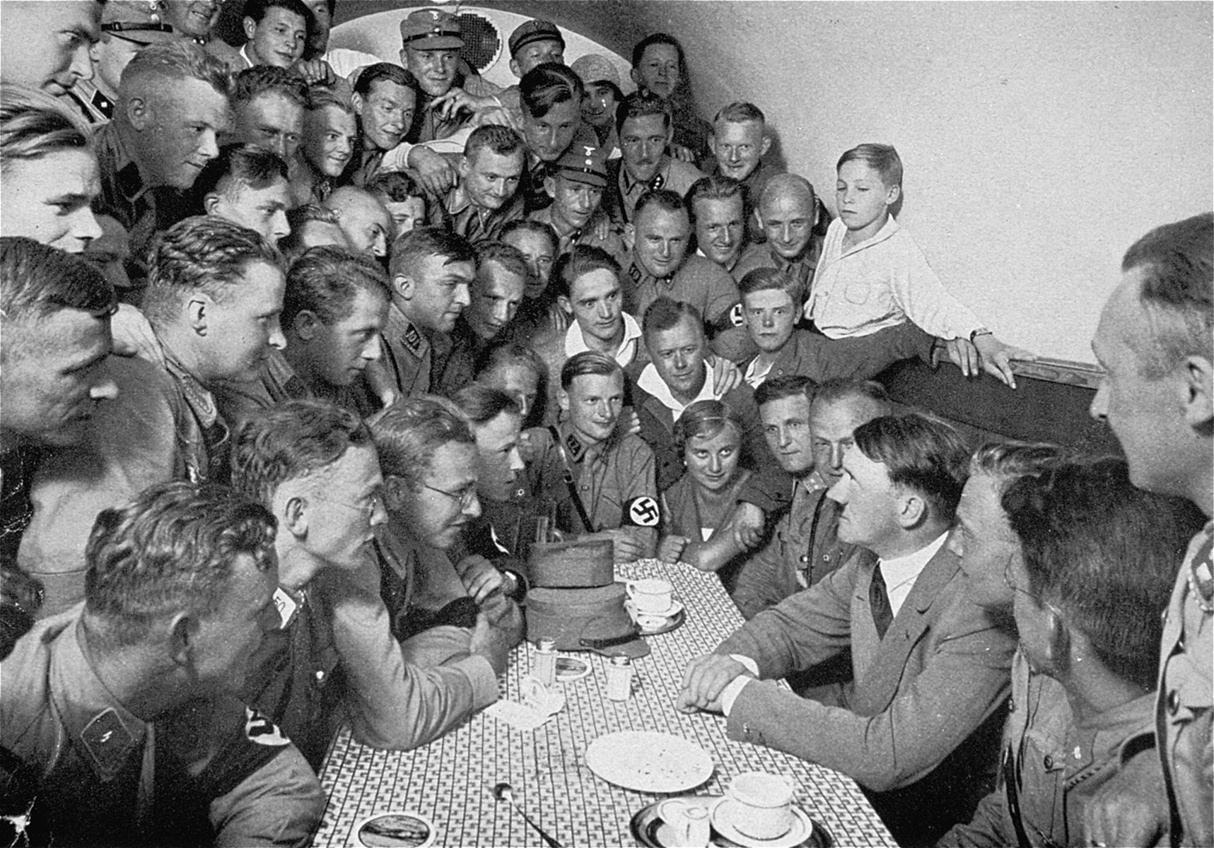 Adolf Hitler speaks to a group of enthralled followers in the basement canteen of the Munich Brown House, a hostel for SA men.