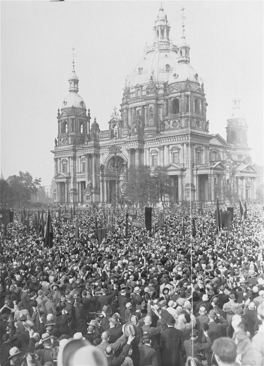 Supporters of the Socialist Party of Germany (SPD) cheer as M. Loebe, the former president of the Reichstag, delivers a speech in the Lustgarten in front of the Berlin Cathedral, condemning Adolf Hitler and the Nazi Party.