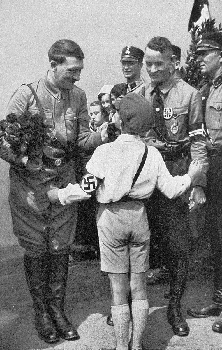 Hitler accepts a bouquet from a young admirer during the presidential elections of 1932.  The man pictured second from the right has been identified as Friedrich Karl Florian, Gauleiter of Duesseldorf.