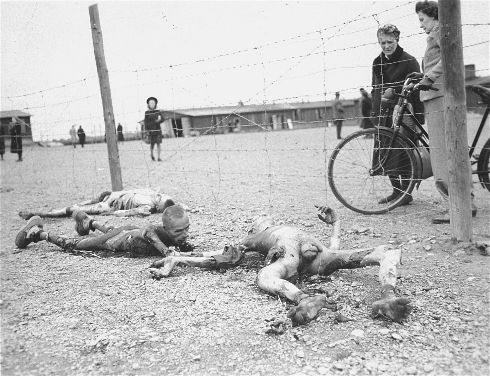 "Horrified German civilians forced to come to the camp, examine the corpses of prisoners murdered by the SS during the evacuation of the Leipzig-Thekla concentration camp.  The inscription on the back of the photograph reads, ""Thekla, near Leipsig [sic] Ger. 1945."""