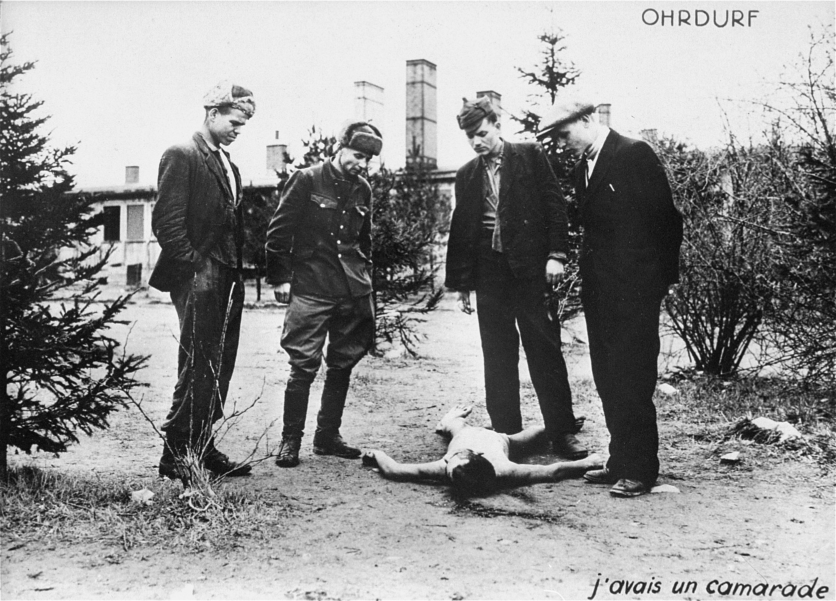 Survivors in Ohrdruf beside the corpse of one of their friends.