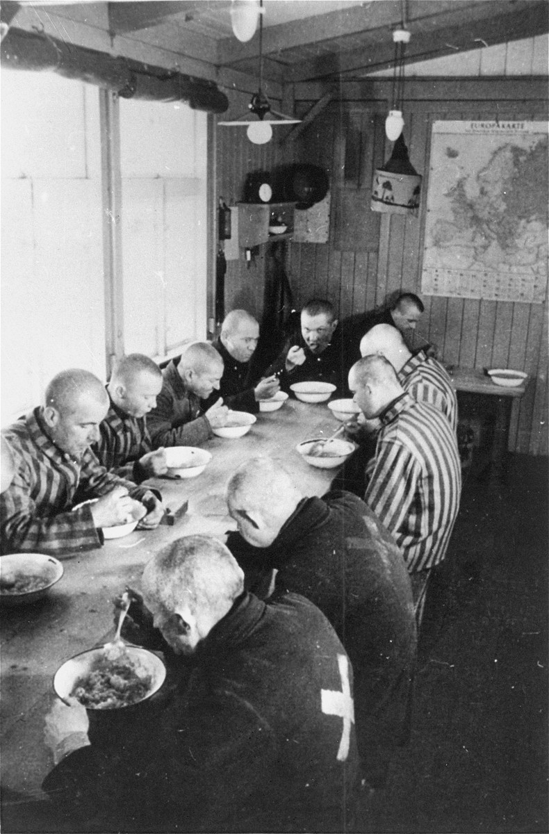 Sachsenhausen prisoners, wearing different types of uniforms, eat a meal in the mess hall of the camp.