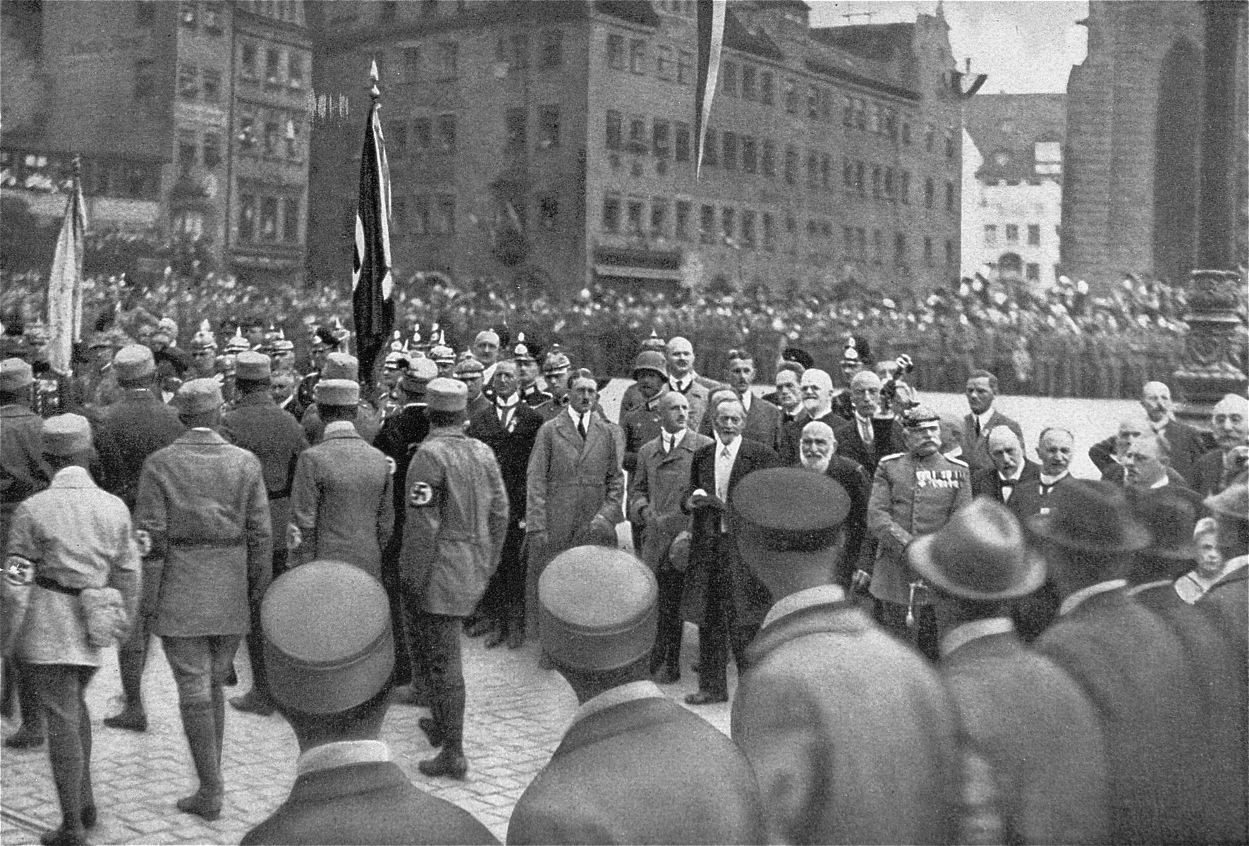 Adolf Hitler, Julius Streicher and other dignitaries review passing Nazi Party members at the Deutscher Tag [German Day] celebration in Nuremberg.  The German Day rally was the prototype of the official Nazi Party Day rallies held in Nuremberg after the seizure of power in 1933.