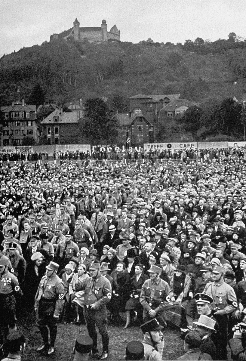 Spectators listen to a speaker during a Nazi rally in a valley below the Coburg fortress.