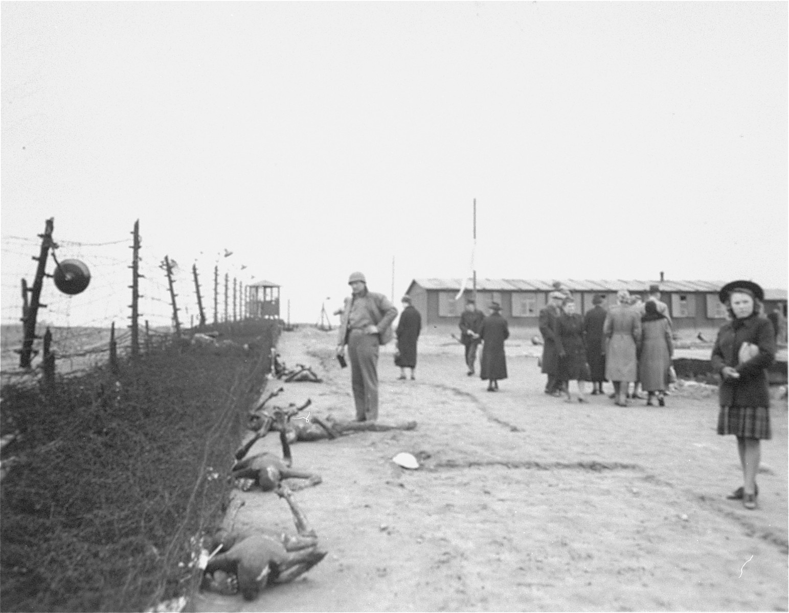 An American soldier and German civilians forced to come to the camp, examine the corpses of prisoners murdered by the SS during the evacuation of the Leipzig-Thekla concentration camp.