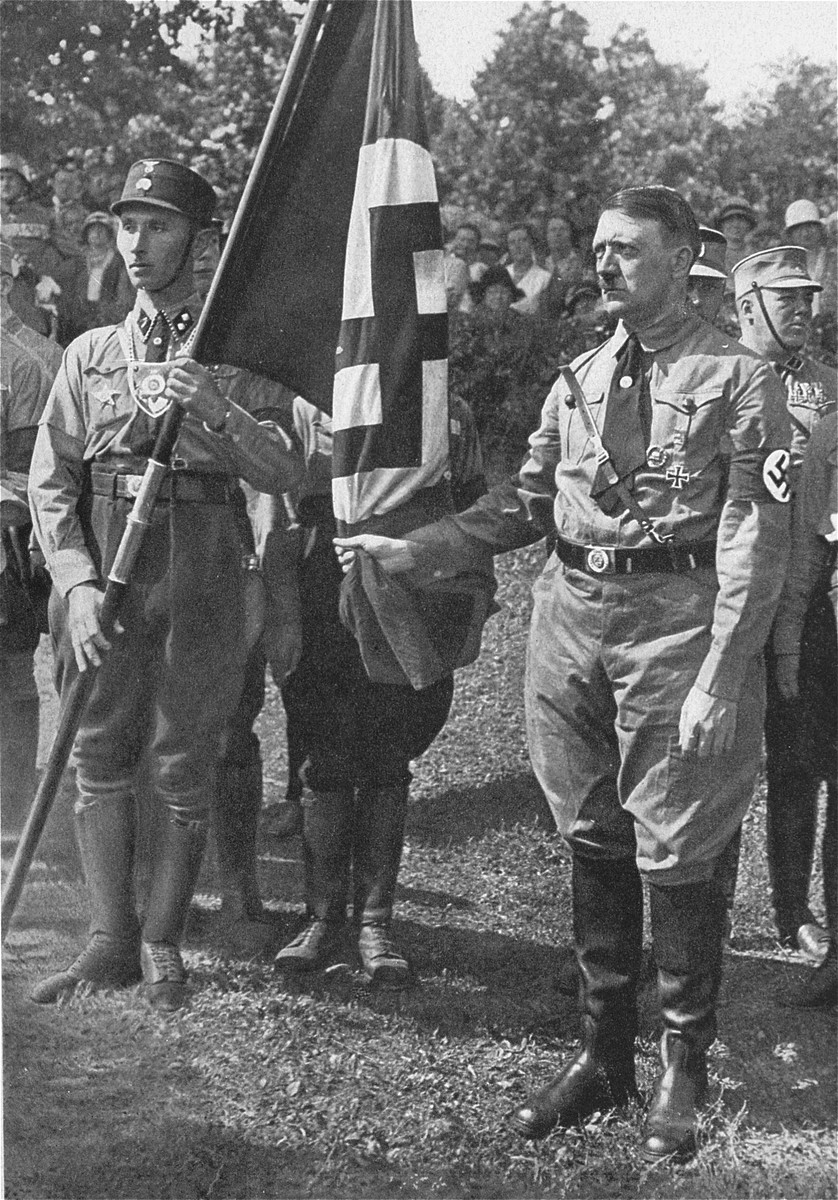 """Hitler poses holding the """"blood flag"""" from the Beer Hall Putsch of 1923 at the fourth Nazi Party Congress."""
