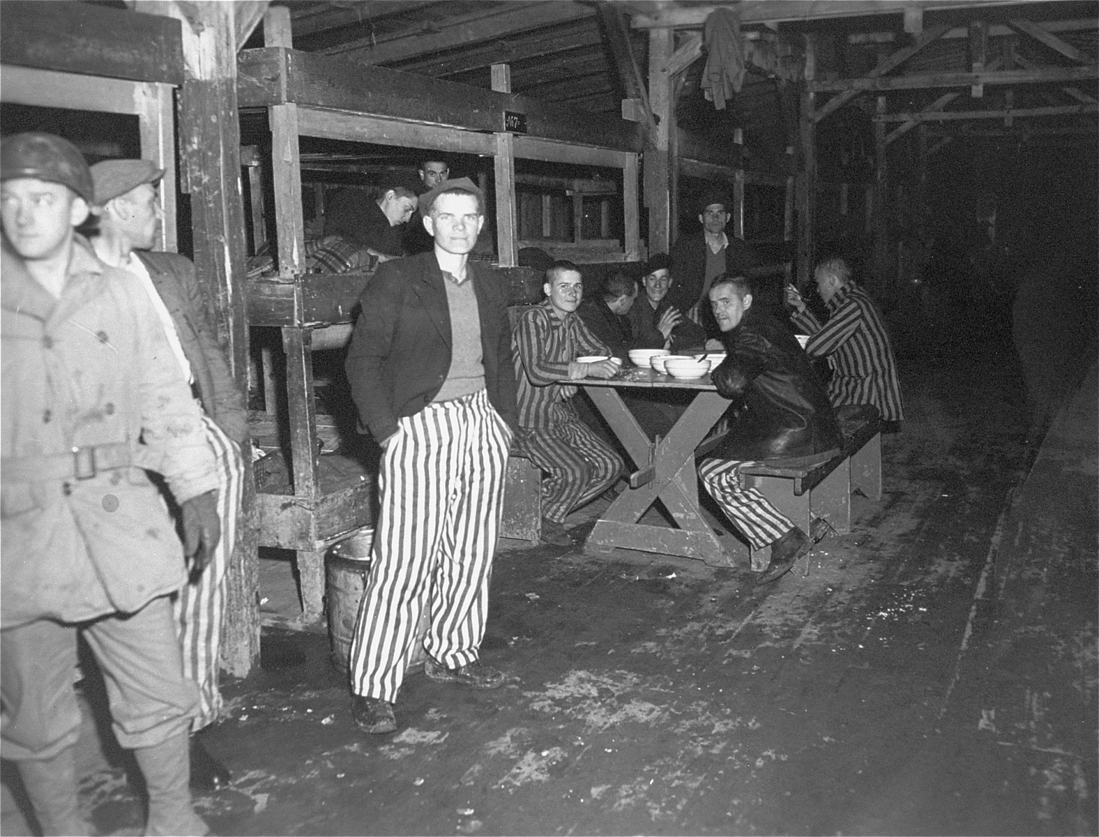 Survivors in a barracks enjoy bowls of soup given to them by the U.S. Army after the liberation of the Buchenwald concentration camp.