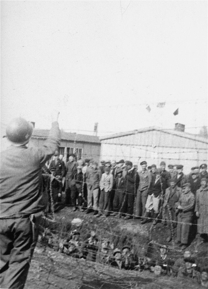 An American soldier throws something over the fence to survivors in the Dachau concentration camp.