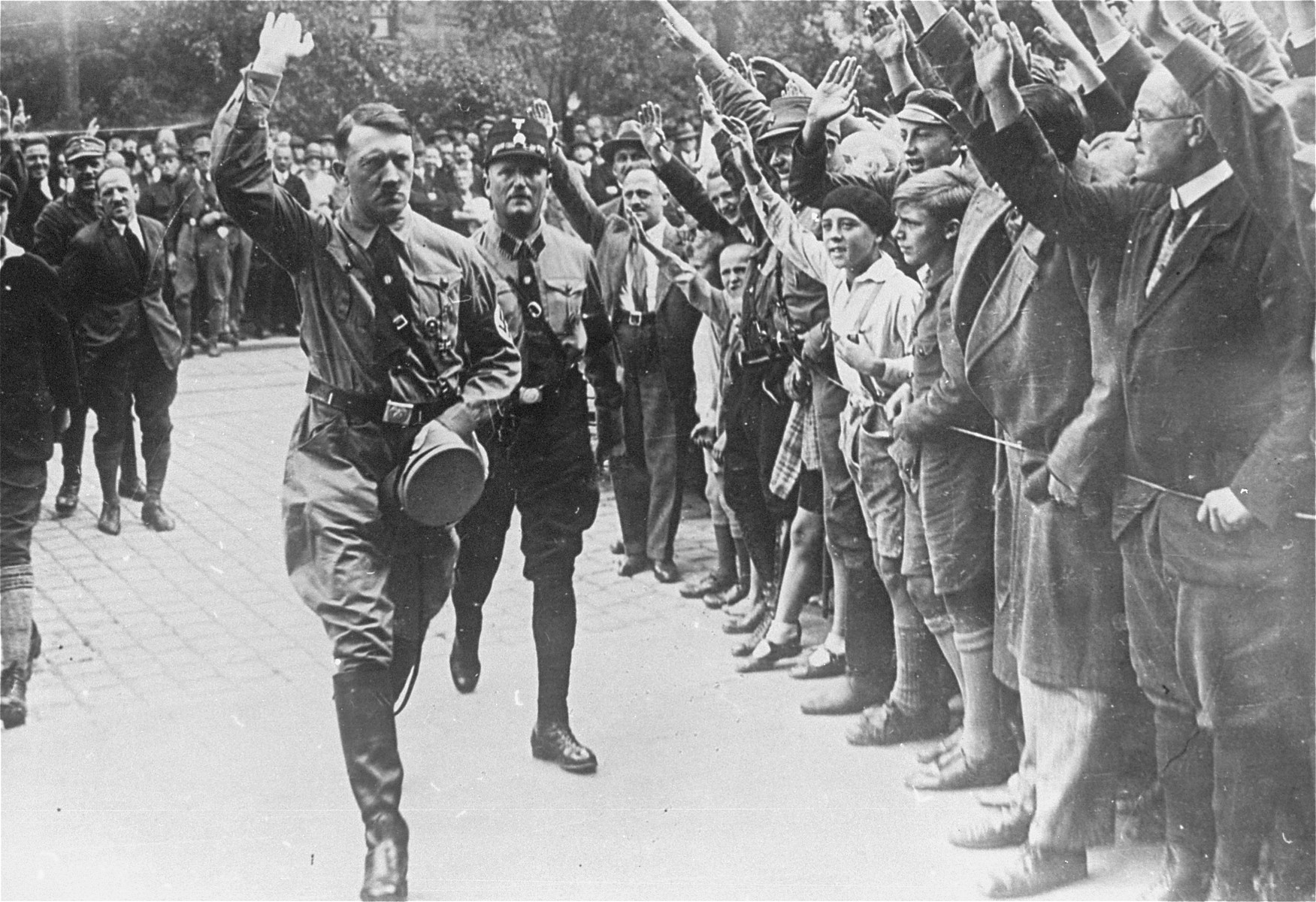 Followed closely by an SS bodyguard, Adolf Hitler greets supporters at the fourth Nazi Party Congress in Nuremberg.