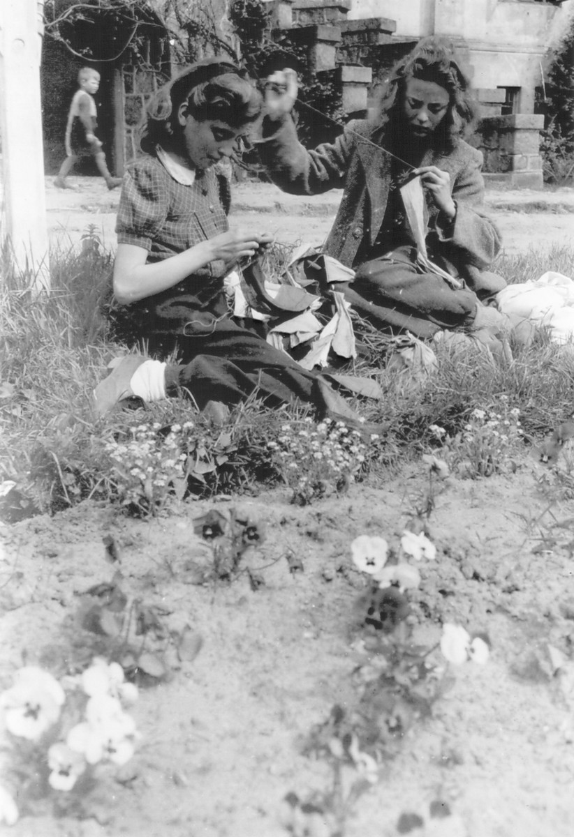 Young girls sew French flags outside at the Hagenow displaced persons camp.