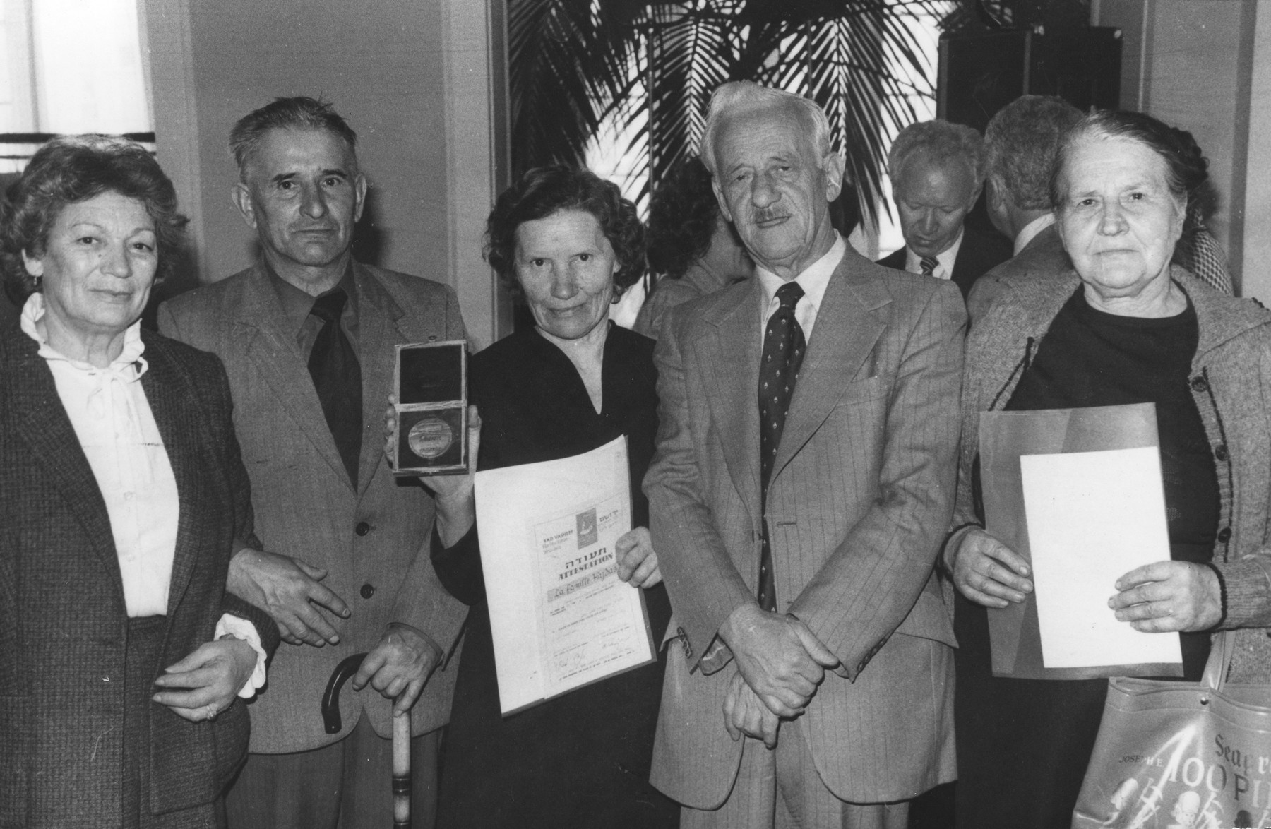 Marysia Sawicka is awarded the Righteous among the Nations medal from Yad Vashem for her assistance to Polish Jews during the war.    Among those pictured are Warsaw ghetto fighter, Stefan Grajek (second from the right) and his wife, Uta Grajek (far left).  Marysia Sawicka is pictured in the center.