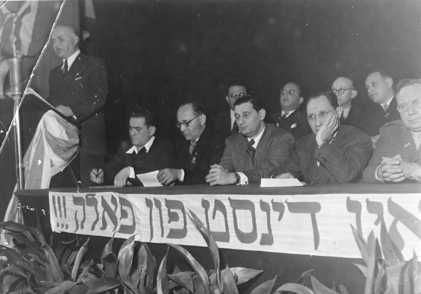 """Jewish leaders attend a post-war Zionist conference in Munich.    Among those pictured is Joseph Schwartz (third from the right).  The Yiddish banner in front of the dias reads, """"In service of the Jewish people."""""""