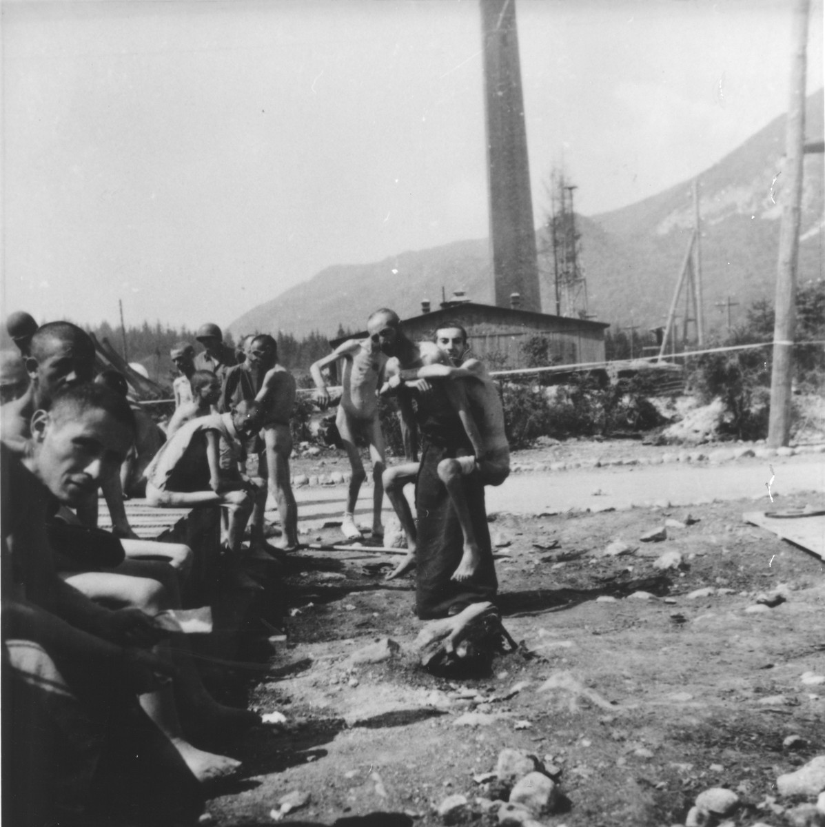 A survivor carries a weaker fellow to the latrine, which American soldiers built for them.  The camp crematorium looms in the background.