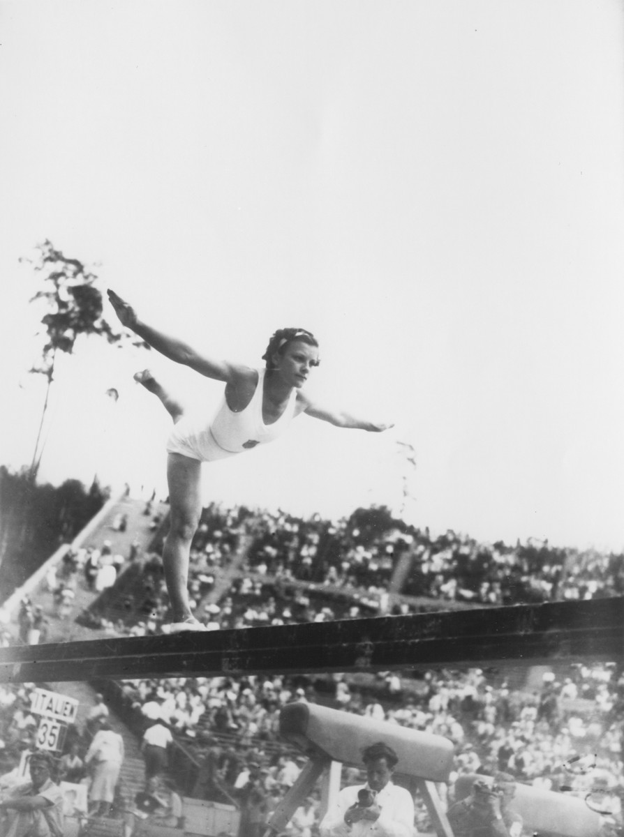 An American gymnast competes in the balance beam competition at the 11th Summer Olympic Games.