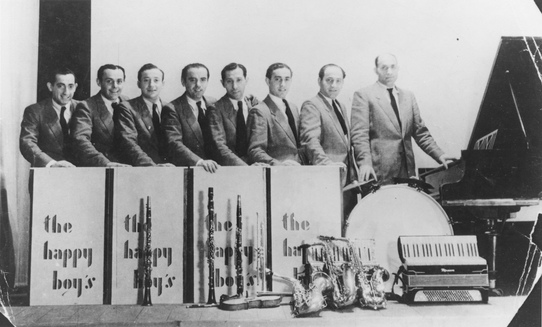 """Group portrait of the members of """"The Happy Boys"""" swing and jazz band which performed at DP camps throughout Germany from 1945-49.  Many had previously been musicians in the Lodz ghetto.  Pictured from left to right are: Sam Spaismacher, Henry Eisenman, Abraham Mutzman, Chaim (Henry) Baigelman, Elek Silberstein, Itchak Lewin, Abraham Lewin, and Josel Lewin."""