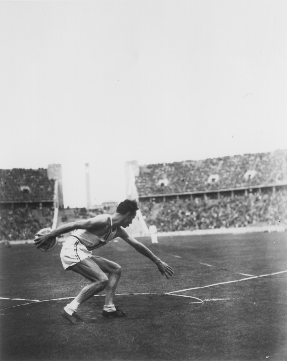 An American man competes in the discus competition at the 11th Summer Olympic Games.