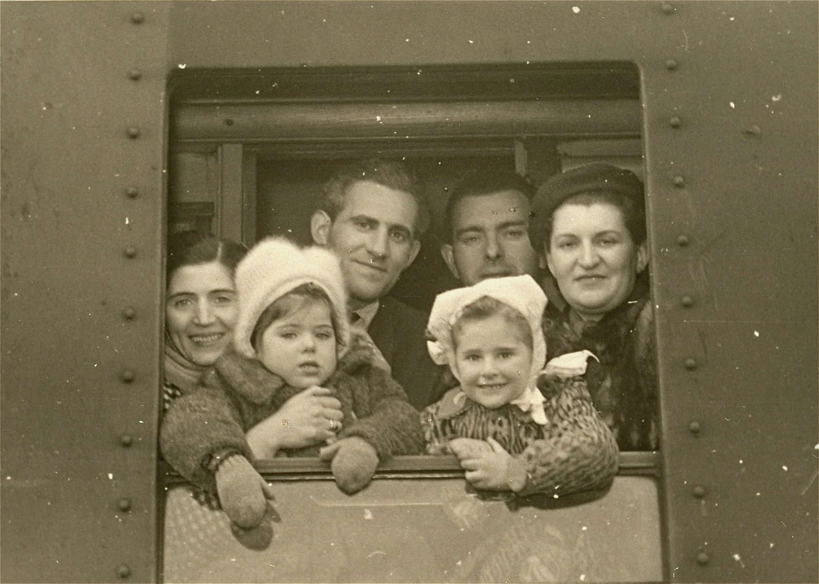 Jewish DPs looks out from the window of a train as they depart for the port of Bremen, on the first leg of their trip to the U.S.  Pictured, from left to right; Hanka Frum, holding her daughter, Sara; Nathan Katz; Moszek Frum; daughter of Nathan Katz; Mrs. Katz, holding her daughter.