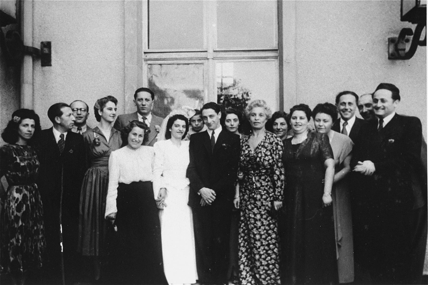 The wedding of Alice and John Fink (center) in the Bergen-Belsen DP camp.  Also pictured are Peggy and Egon Fink (left), Rabbi Helfgott (extreme right), and to the right of John Fink, Ava Gottlieb, Herbert and Frieda Treitel.