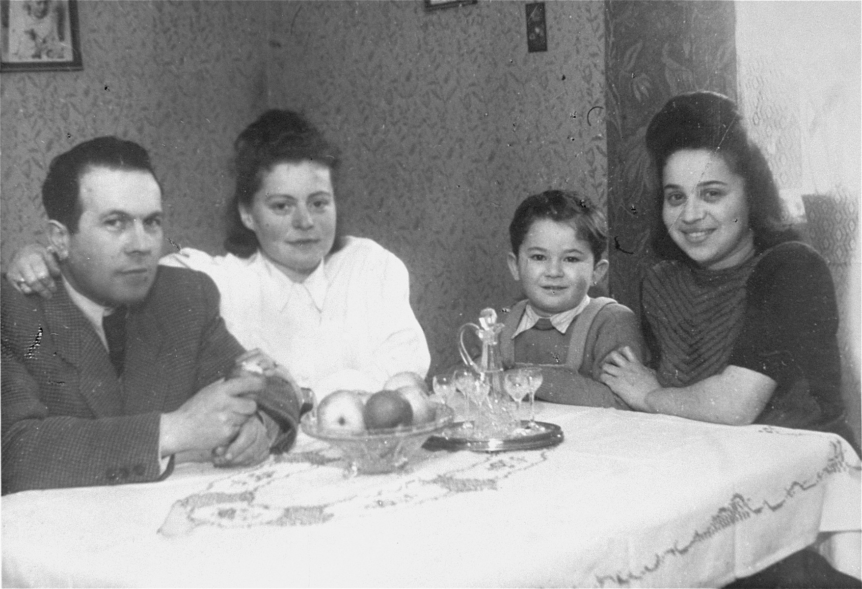 Jurek Kaiser sits at a table with friends and relatives in the Bergen-Belsen displaced persons camp.  Pictured from left to right are Shmulek and Lola Mandelbaum, Jurek Kaiser, and Mania Zaks (Jurek's aunt).