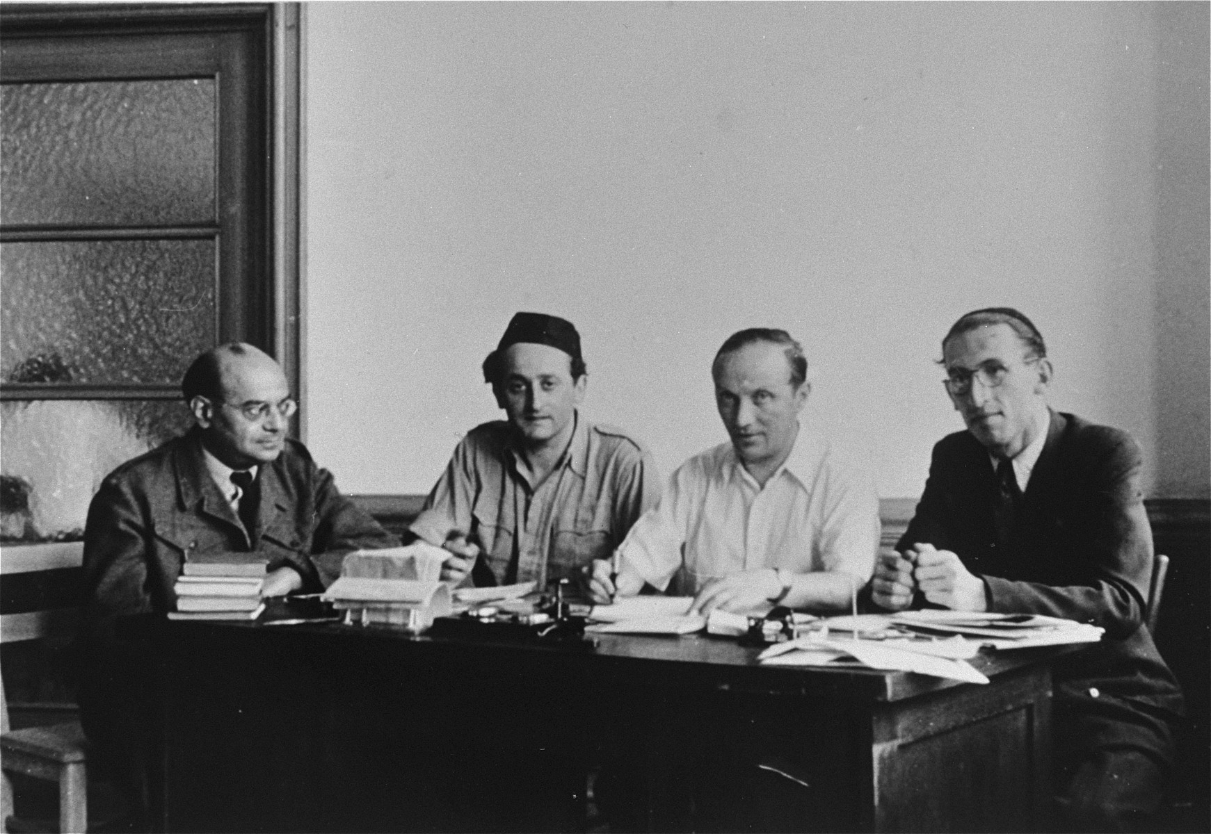 Four members of the Central Jewish Committee for the British Zone of Germany are seated in an office.  Pictured from left to right are: unknown; Rabbi Zvi Helfgott (later Zvi Asaria); Josef Rosensaft; and Rabbi Joseph Asher.