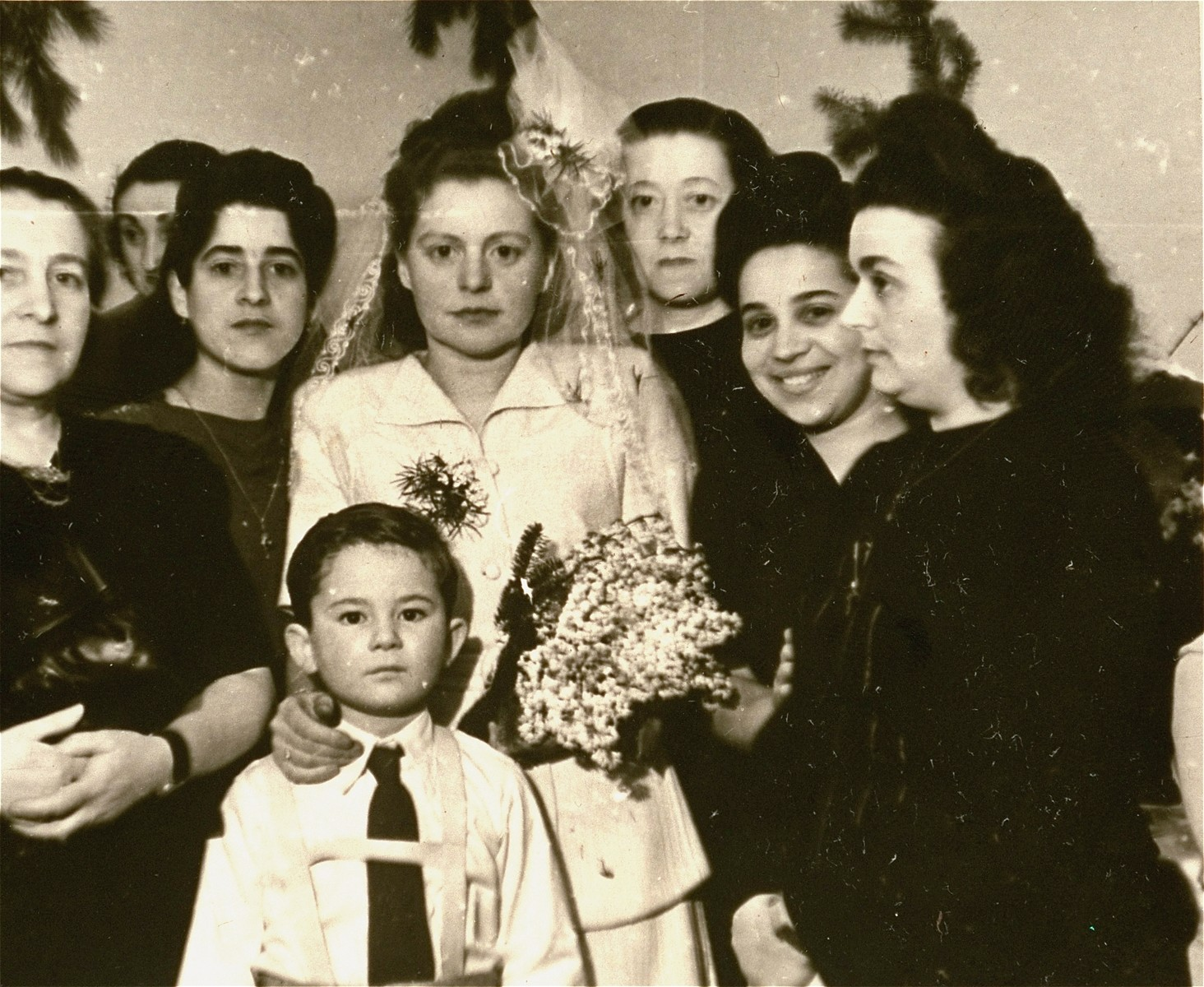 Group portrait of the Mandelbaum wedding party at the Bergen-Belsen displaced persons camp.    Among those pictured are Jurek Kaiser (the child); Lola Mandelbaum (the bride) and Mania Zaks (second from the right).
