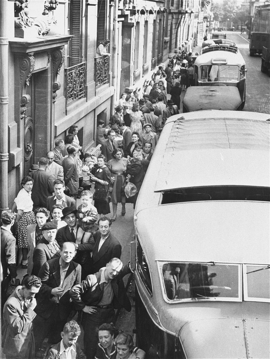 Jewish DPs wait on a street in Paris to board a convoy of buses that will transport them to Marseilles, on the first leg of their journey to new homes in South America and Australia.
