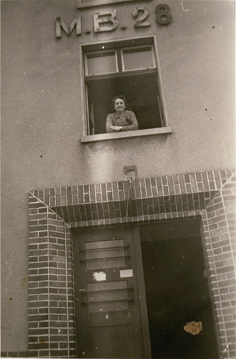 Masza Kuropatwa Sompolinski looks out the window of her living quarters, block 28, at the DP camp in Bergen-Belsen.