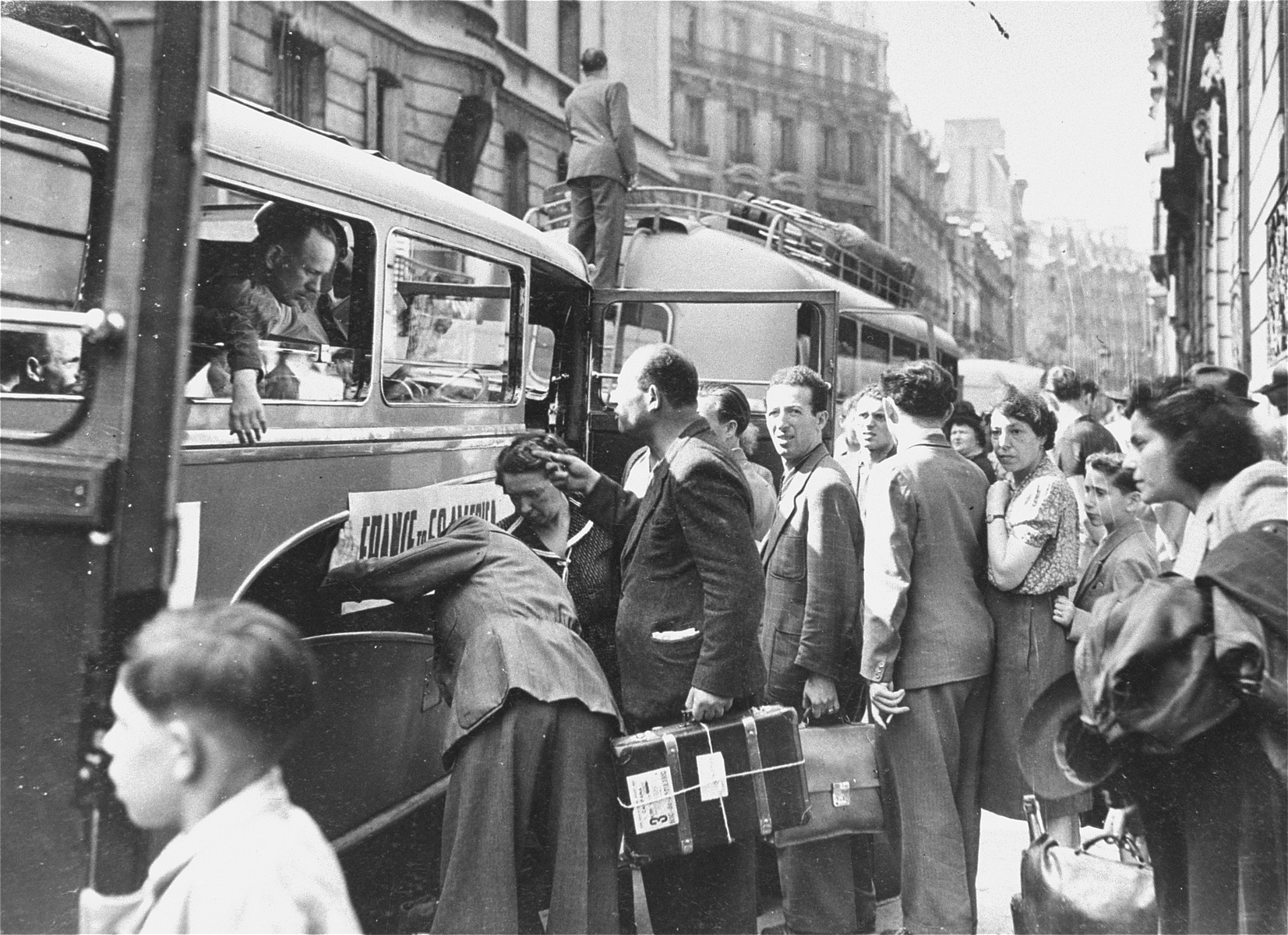 Jewish DPs wait in line on a street in Paris to board a convoy of buses that will transport them to Marseilles, on the first leg of their journey to new homes in South America and Australia.