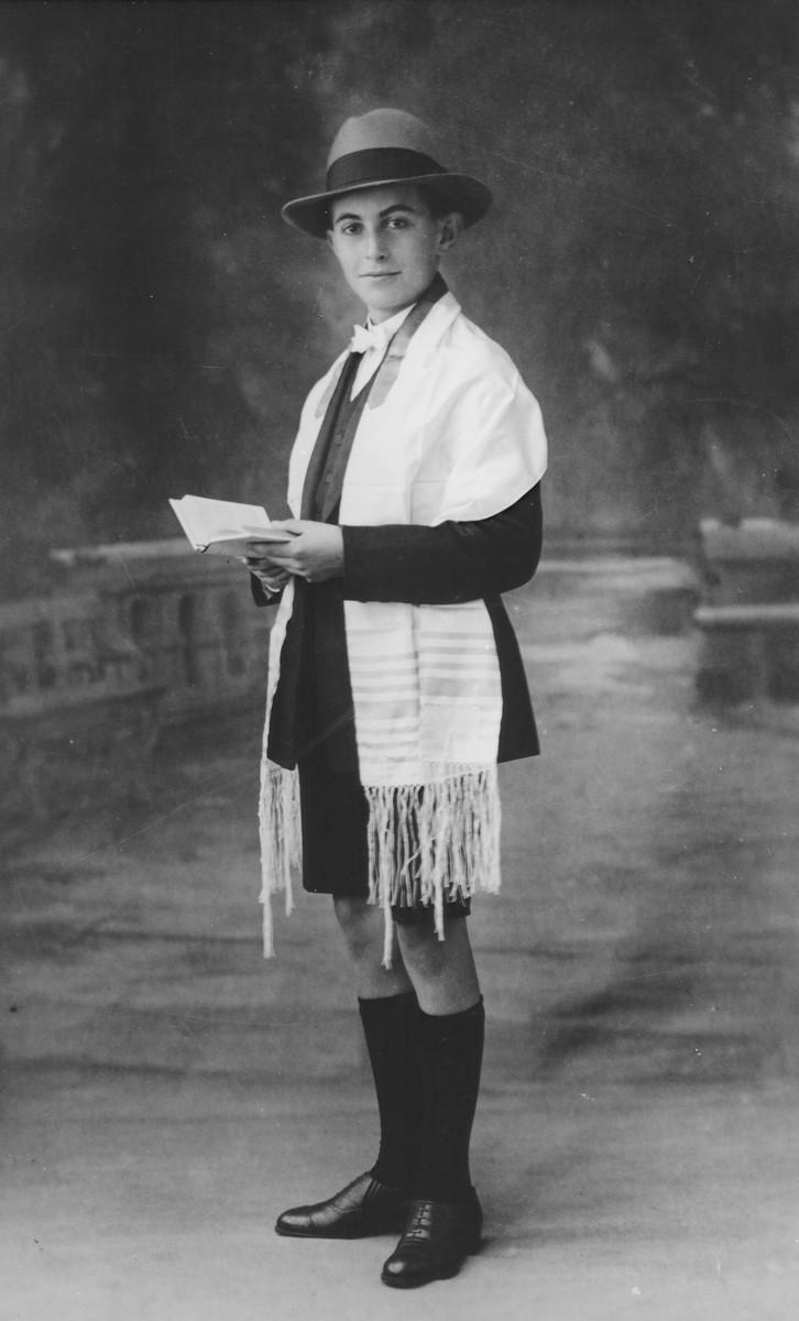 Bar mitzvah portrait of a Jewish boy in a tallit holding a prayer book.