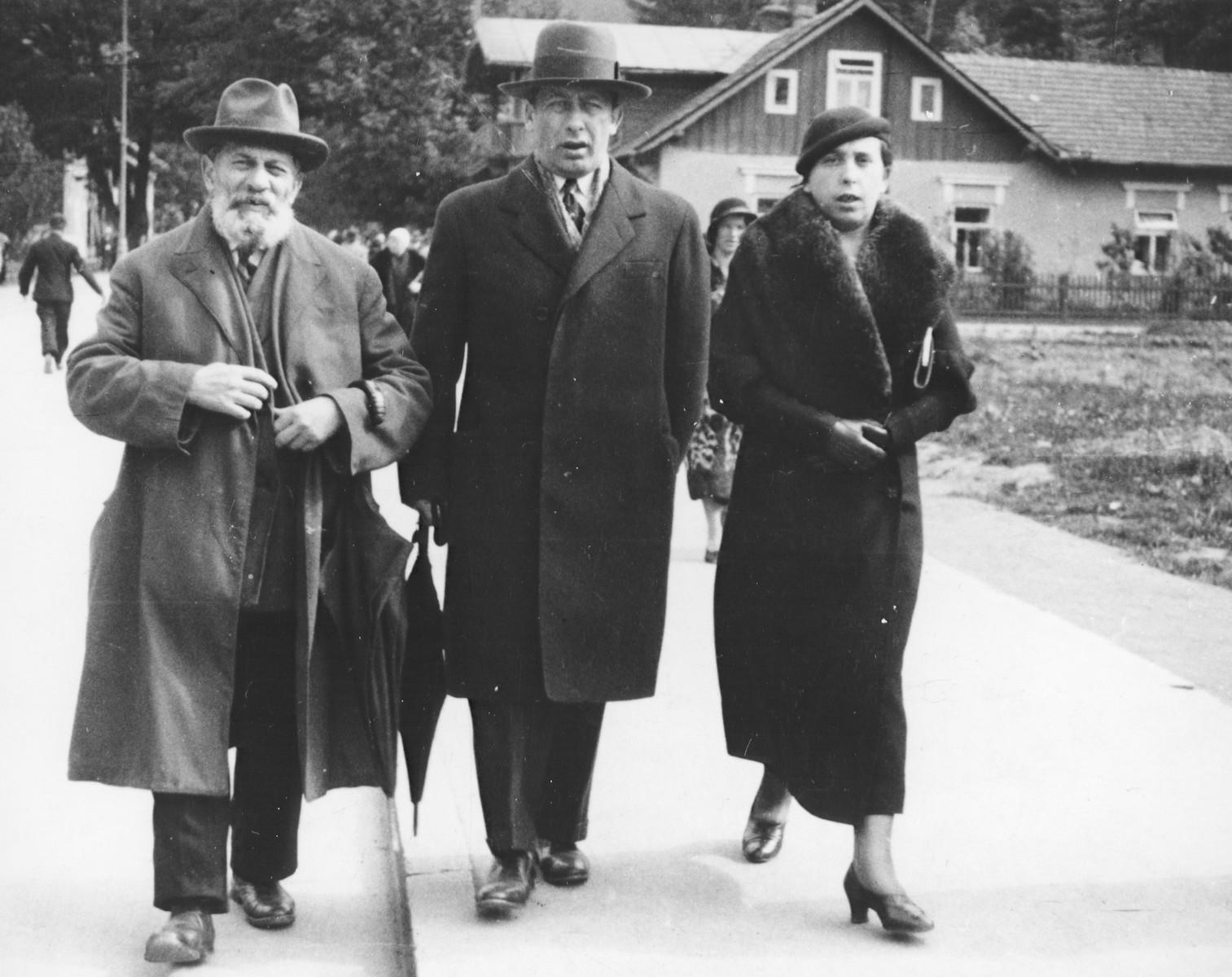 Three Polish Jews enjoy a stroll down a street in Krynica.