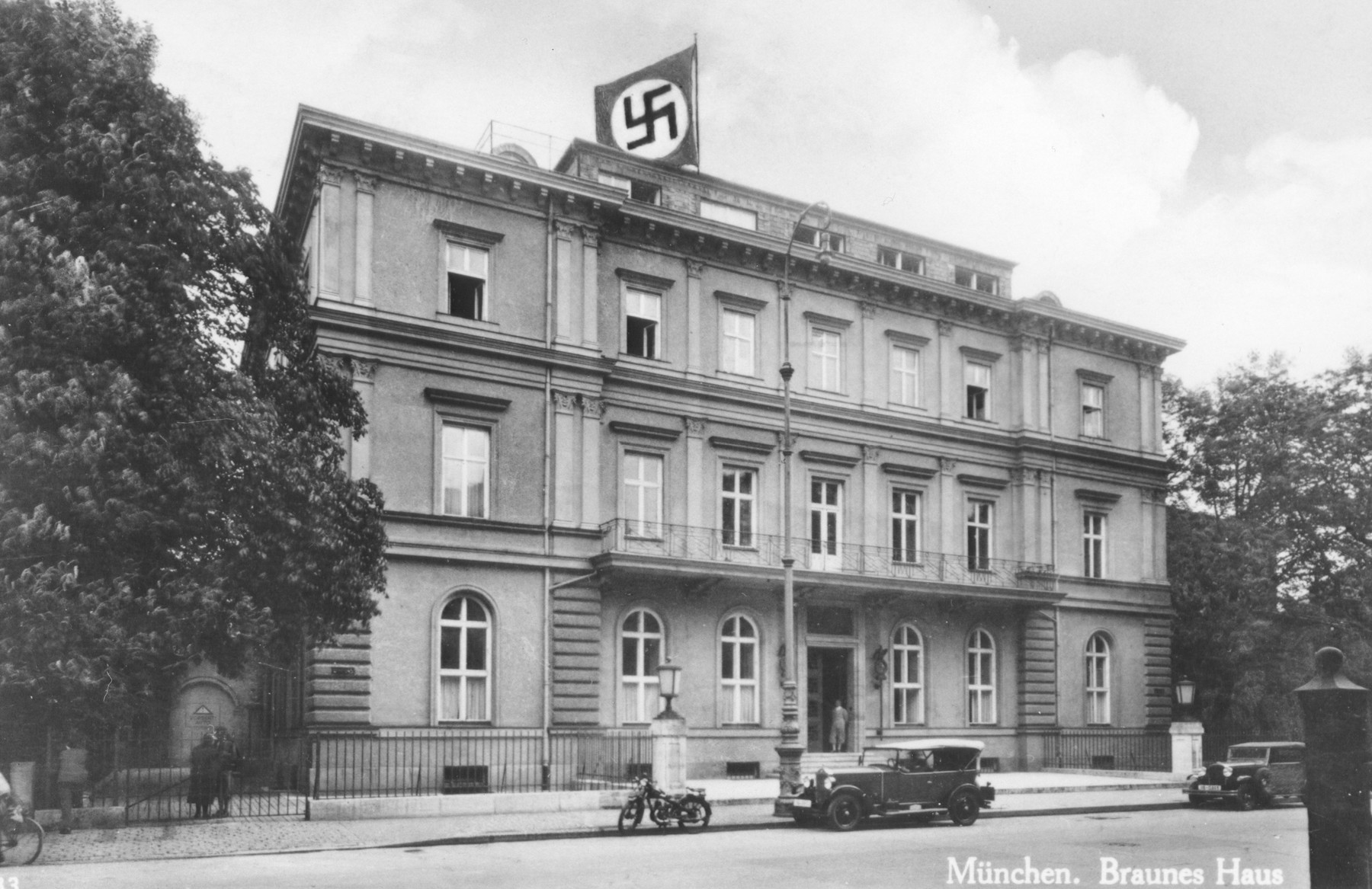 "Exterior view of a swastika flag flying over the Brown House, the Nazi party headquarters, in Munich.   The picture was on a postcard, dated May 28, 1935, which was was addressed to a Dr. Cohen of Chicago, and says that Germany is a ""peaceful land."""