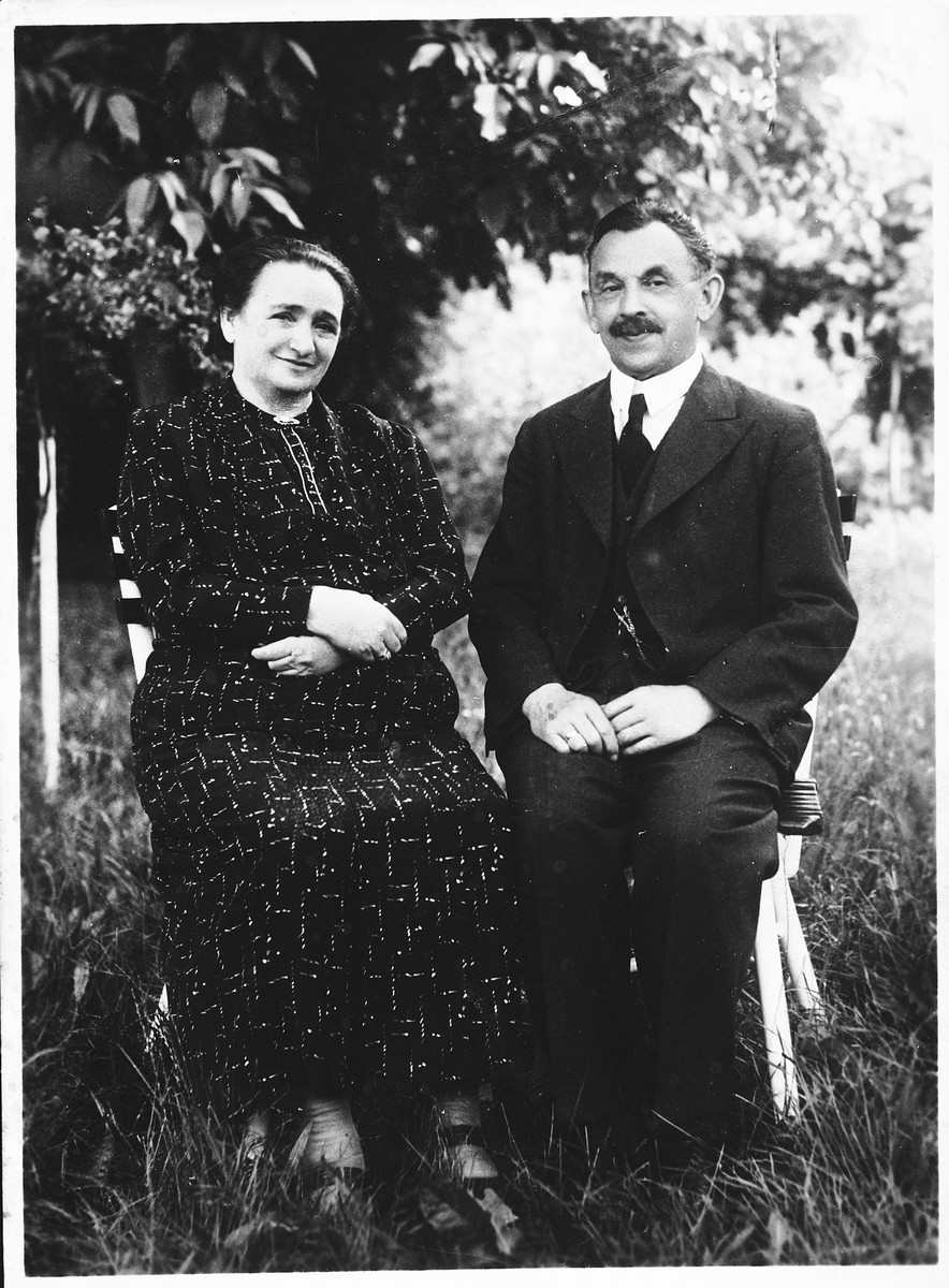 A Jewish couple sits outside on chairs in a town in Bohemia.  Pictured are Zigmund and Berta Budlovsky.