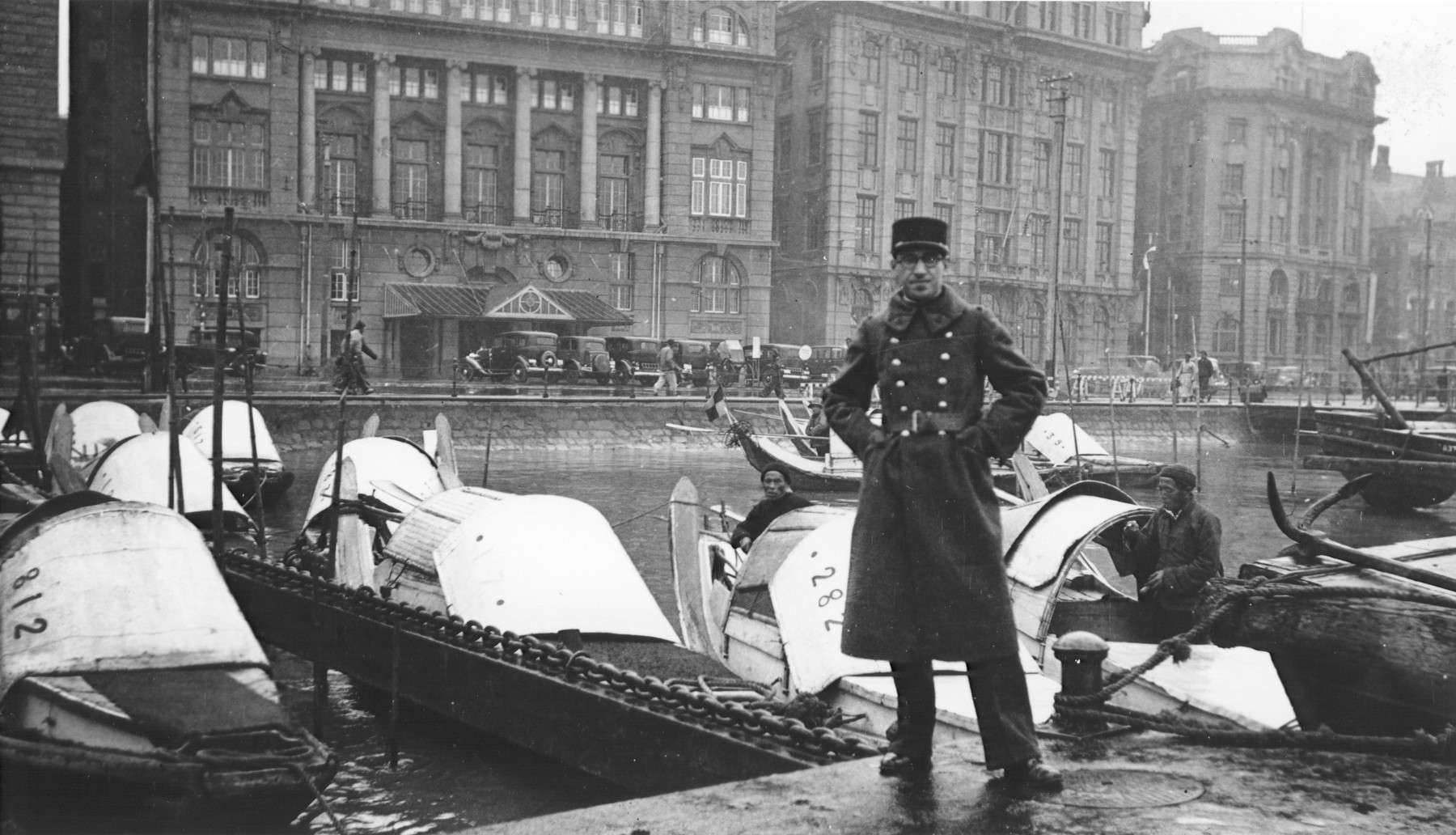 Mr. Frenkel, a Jewish soldier in the French army, poses next to small boats on a canal in Shanghai.