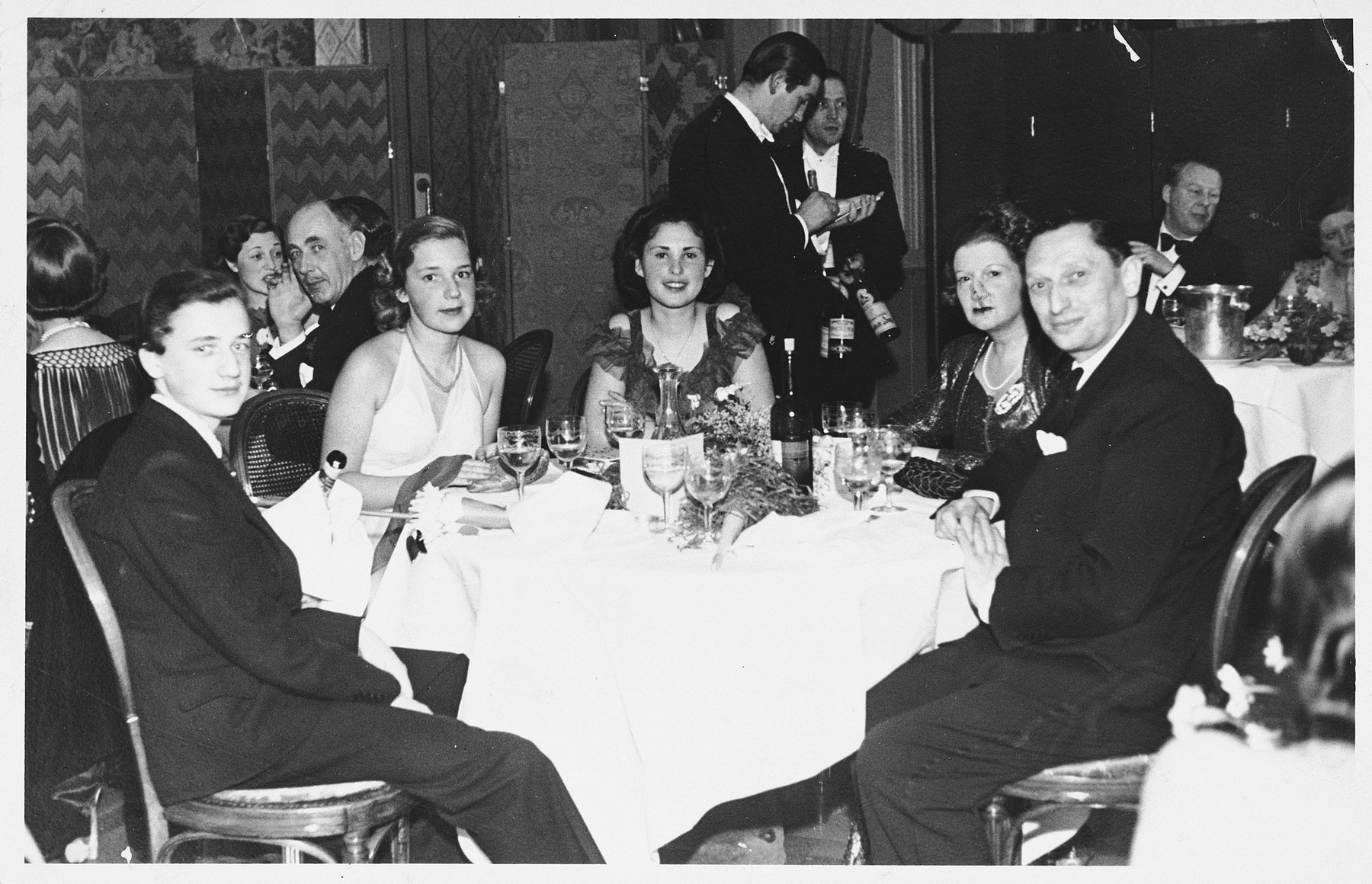 Ella Feuerwerk celebrates New Years with friends at the Carlton Hotel in Saint Moritz, where her father sent her to escape the political situation in Austria.  She is pictured in the center.  Also pictured are Mr. and Mrs. Levy and their niece and nephew, Nina and Karli.