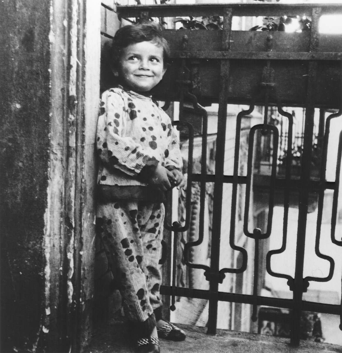 A young girl leans against the railing of the balcony of her apartment.  Pictured is the cousin of the donor.  Her father Shlomo was the younger brother of Joseph Halter.