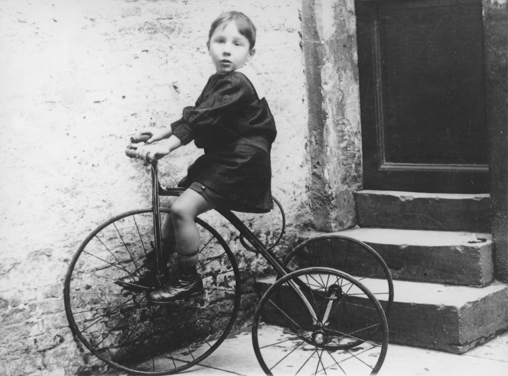 A young Belgian-Jewish boy rides a tricycle.  Pictured is Paul Halter.