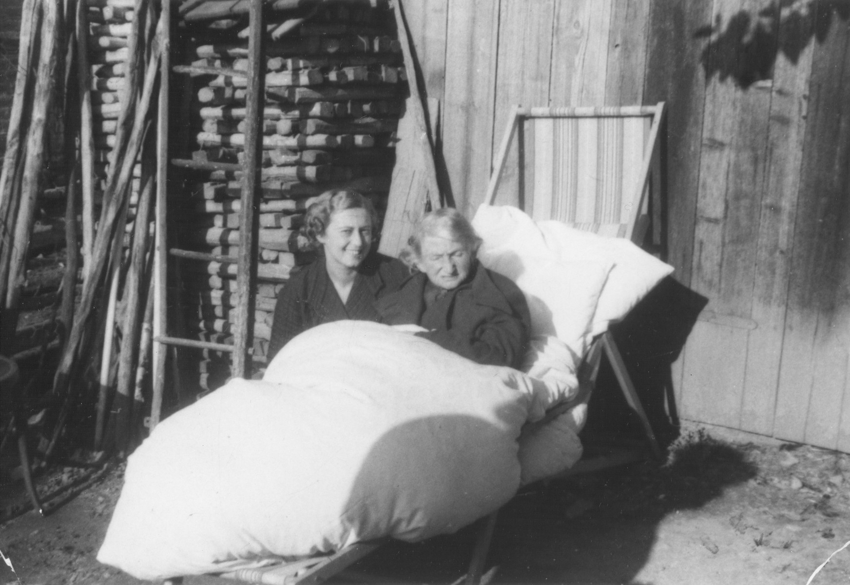Lili Koenig poses next to her mother Sari Vermes who is sitting outside bundled up in comforters and pillows.