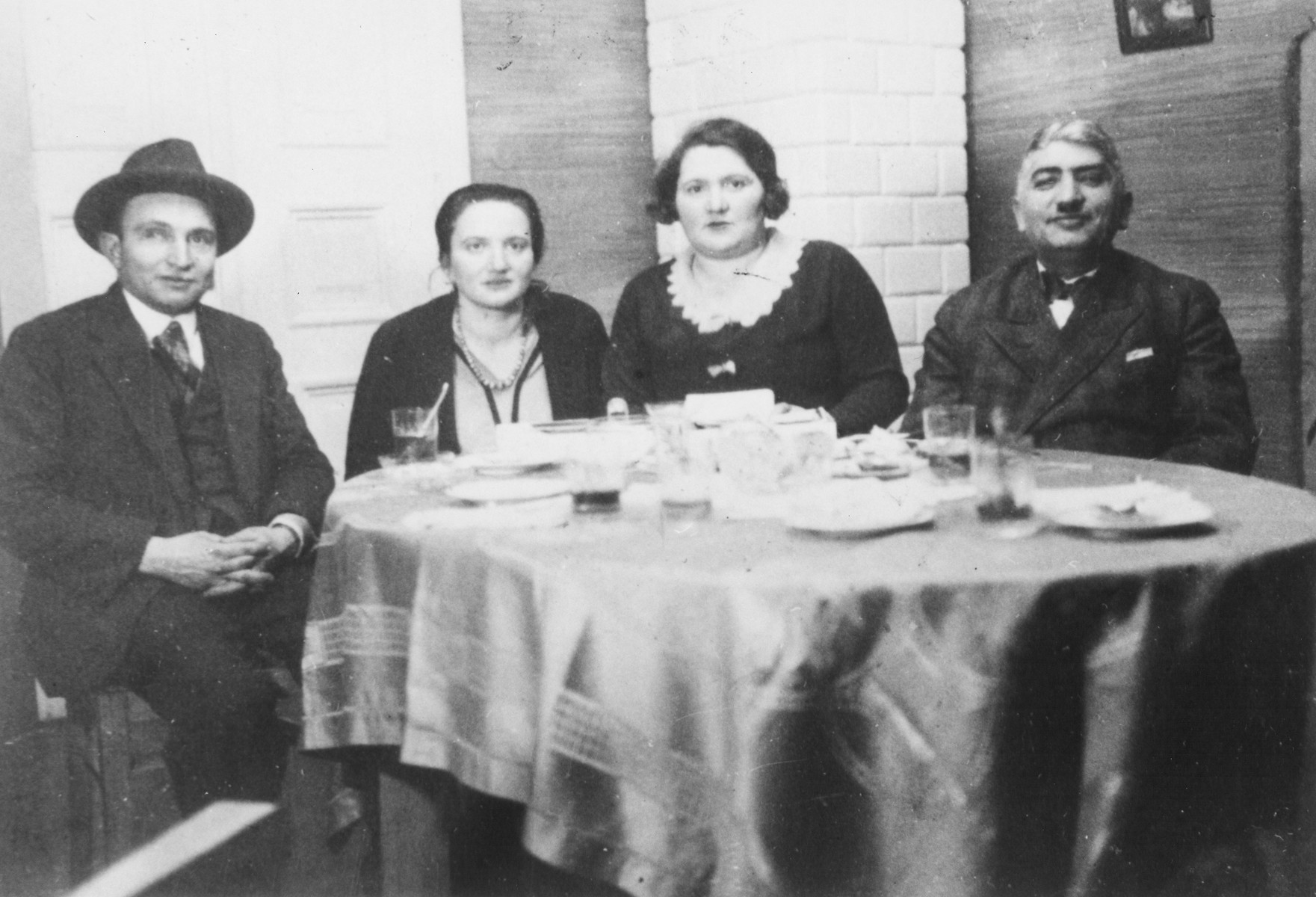 Prewar portrait of a Jewish family sitting at a table.  Pictured are the family of Henry Tovey (originally Choroszcz).  From left to right are Natan Malczer (his uncle), Masia Majerczyk (his aunt), Rozia Choroszcz (his mother) and Nechemia Choroszcz (his father).