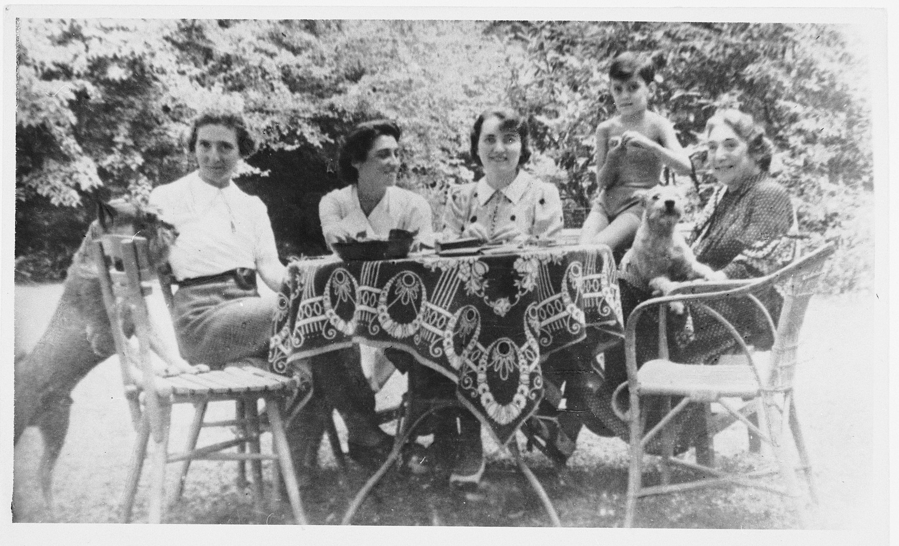 Friends and family gather around an outdoor table in Zagreb, probably 1939.  Pictured from left to right are [unknown], Edith Wohlmuth Rendi (foster mother to Heinz), Sidonie Brecher Bencic (Heinz's aunt), Heinz Brecher, and Else Wohlmuth (mother of Edith).