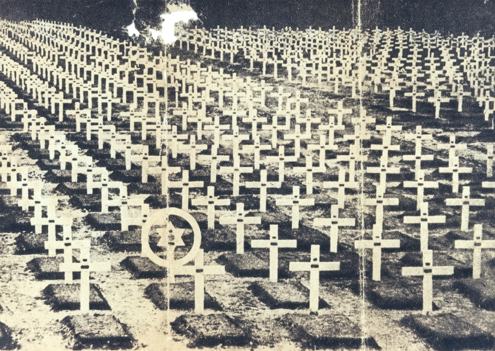 "Obverse of an American antisemitic handbill,  ""The Lone Star of David,"" showing a photograph of a section of a military cemetery in which there are rows of crosses and one Star of David.    Addressed to soldiers, the text  on the other side insinuates that Jews avoid military service, thus placing more responsiblity on  non-Jewish soldiers and increasing their danger of dying in combat."