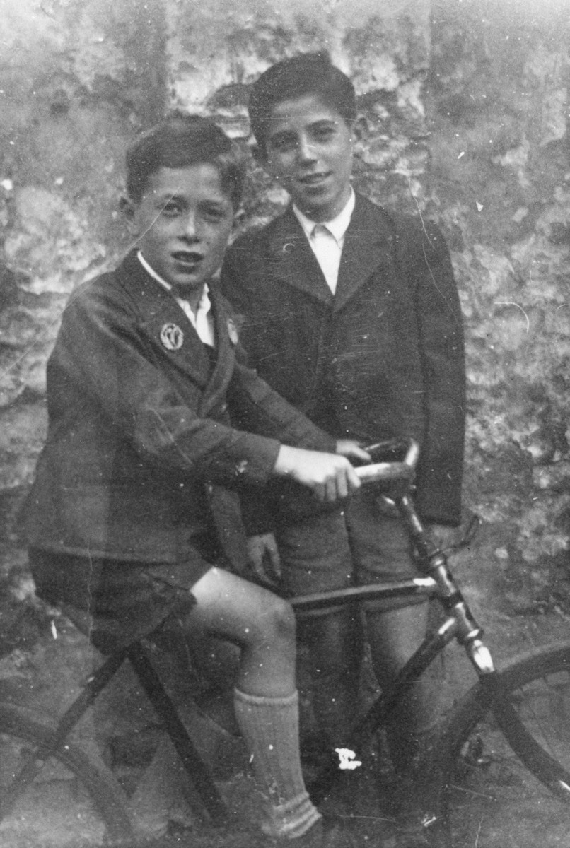 Two Viennese Jewish cousins pose together with a bicycle.  Alfred Traum is on the bicycle.  His cousin Joseph is behind him.  Joseph perished in the Holocaust.