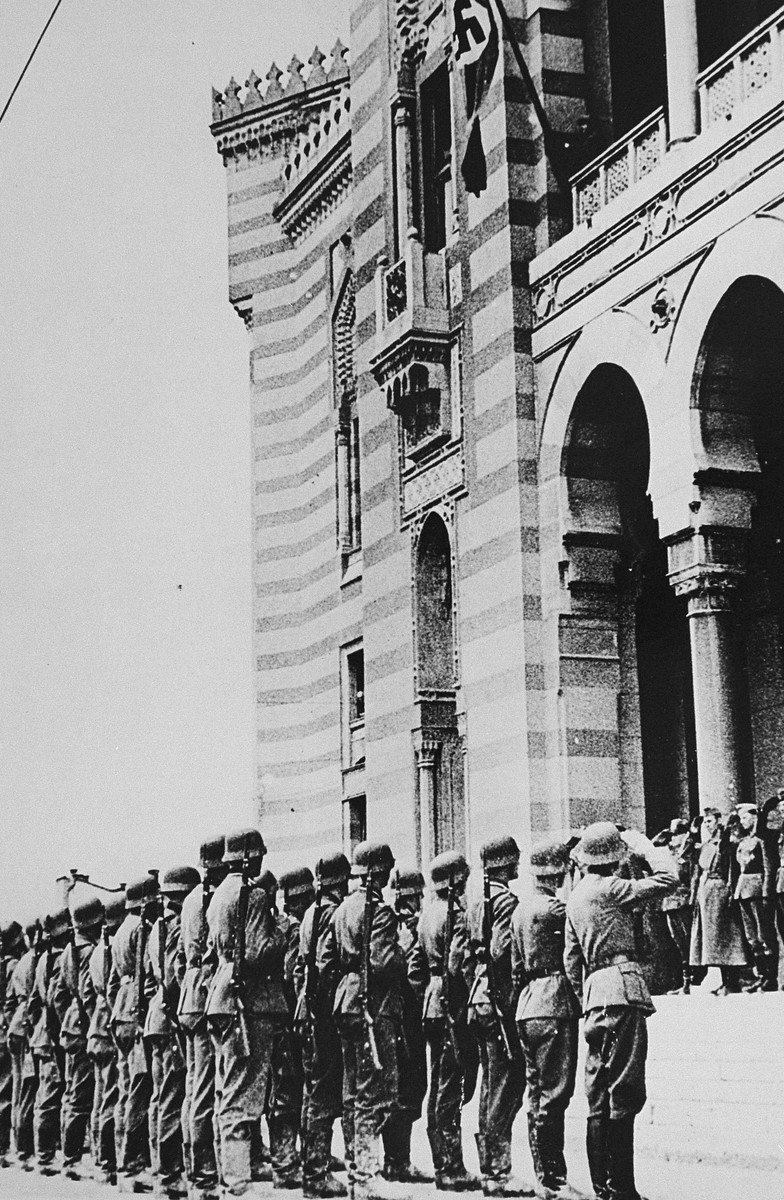 German troops salute during a flag raising ceremony on the balcony of Sarajevo city hall.