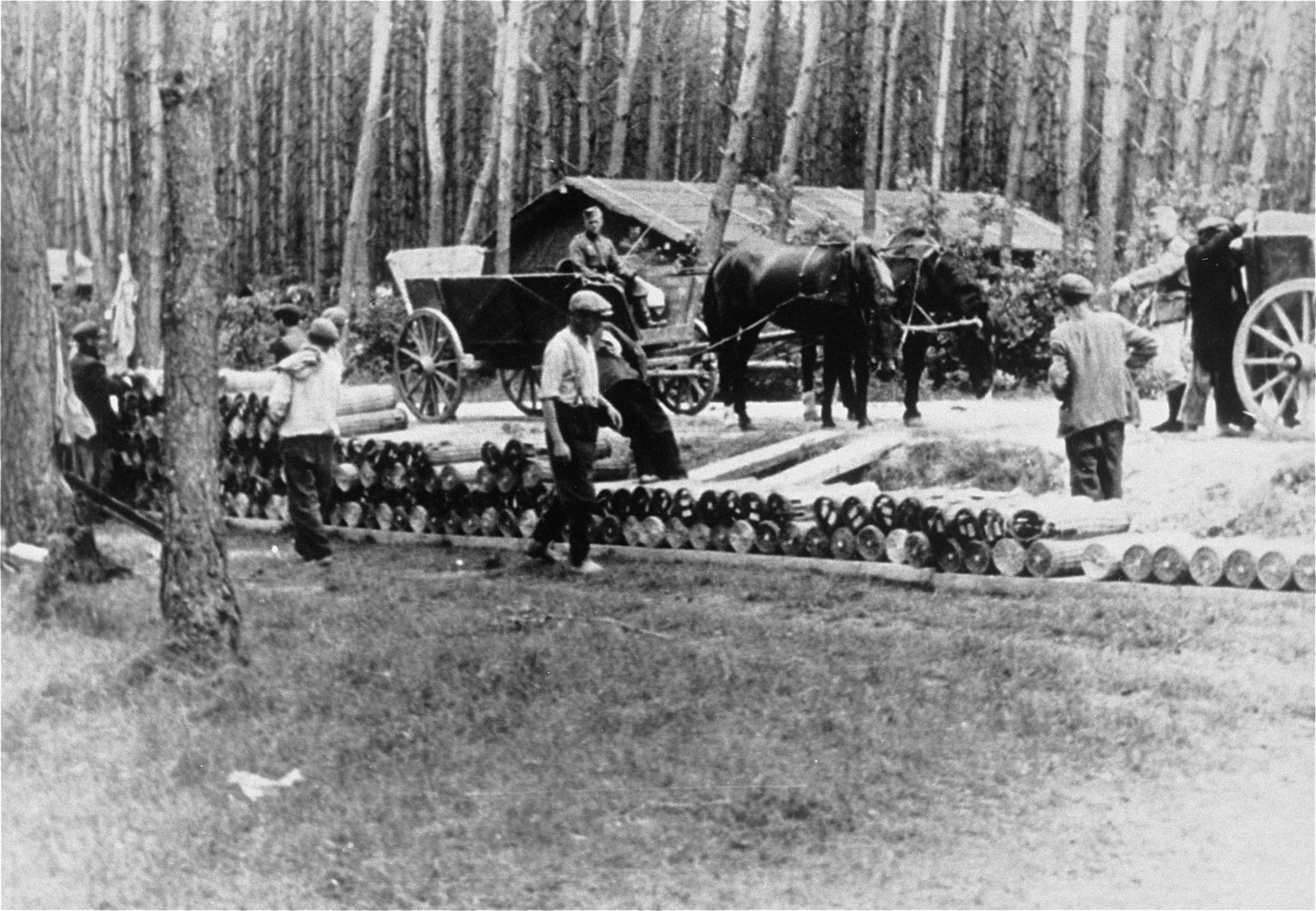 Jews at forced labor stacking artillary munitions.