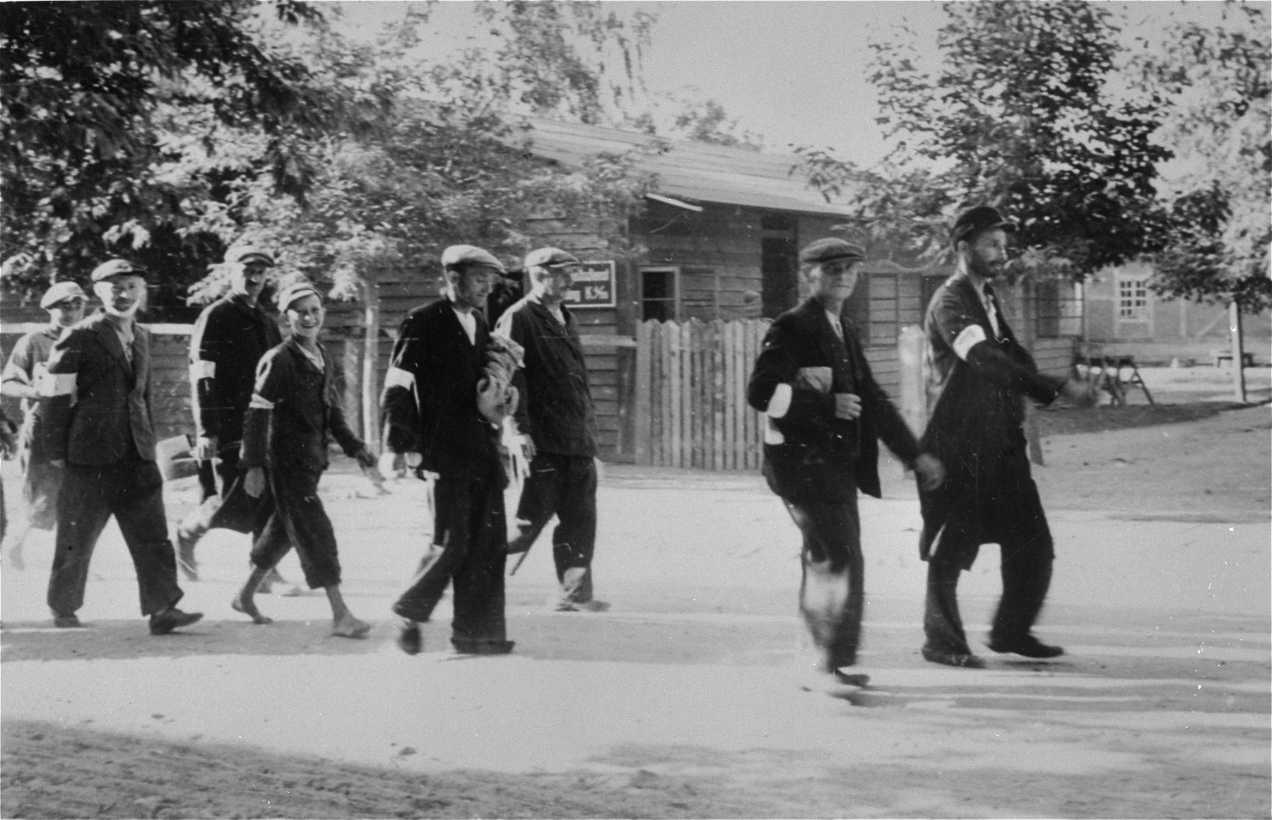 A group of Jewish men and youth who are wearing armbands, are marched to a forced labor site.