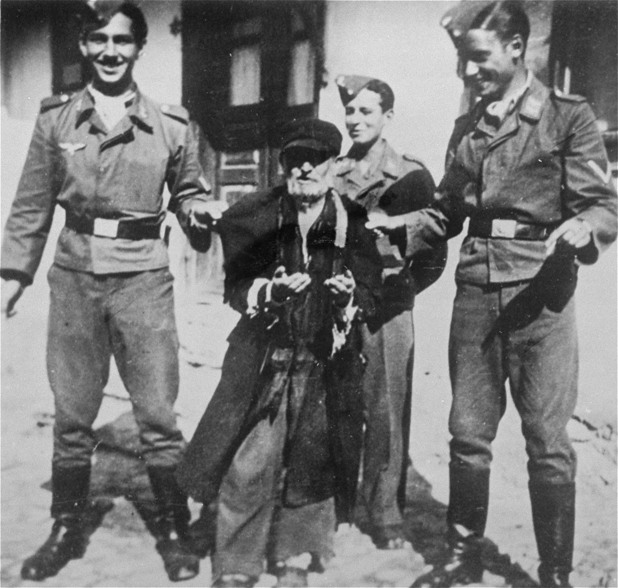 Three young Germans publicly humiliate an elderly Jew in the streets of Krzemieniec.