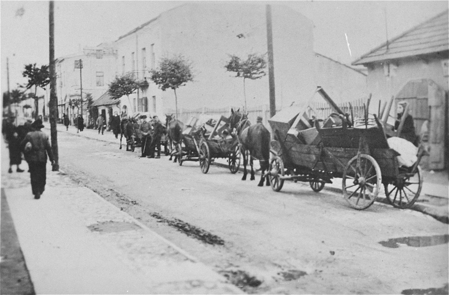 A procession of horse-drawn wagons bearing the belongings of local Jews makes its way down a street in Olkusz.