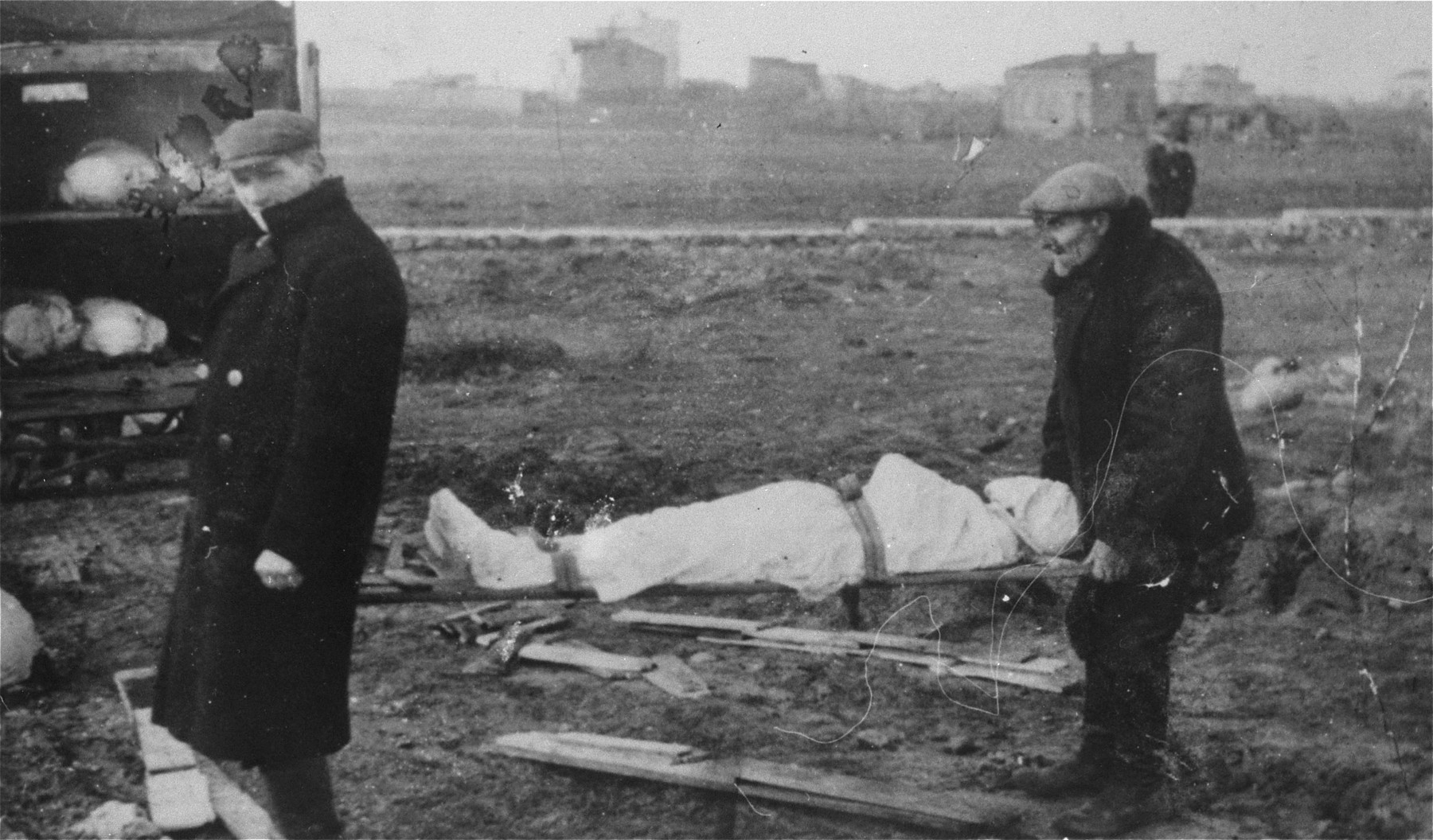 Two men remove a corpse from a truck and carry it to a burial site in the Jewish cemetery in Kutno.